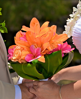 Orange lilies, roses and plumeria with a ti-leaf wrap