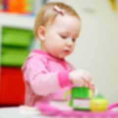 Adorable toddler girl playing with toys