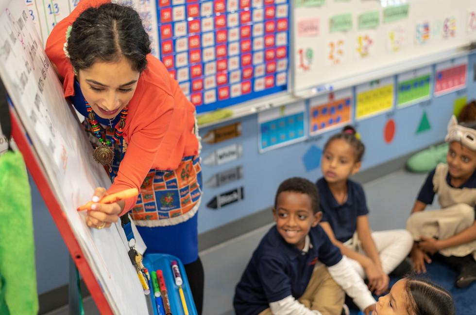 Charter School Teach Writing on Board to Class