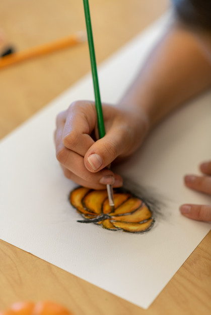 Boy Painting with Watercolors in School