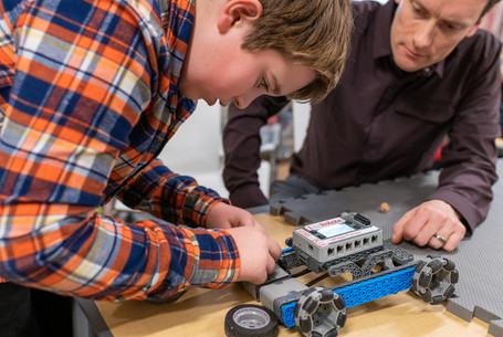 University Prep Boy Building Robot in STEM Class with Teacher