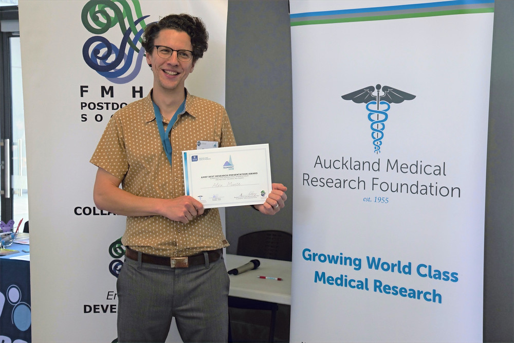 Dr Alex Müntz receives the AMRF Best Oral Presentation prize at SUMMIT2020 and stands in front of banners for AMRF and the FMHS Postdoctoral Society while holding his award certificate