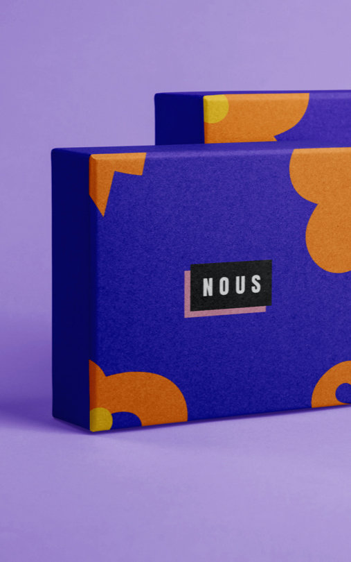 """Two purple product boxes with orange flowers and brand name """"Nous"""""""