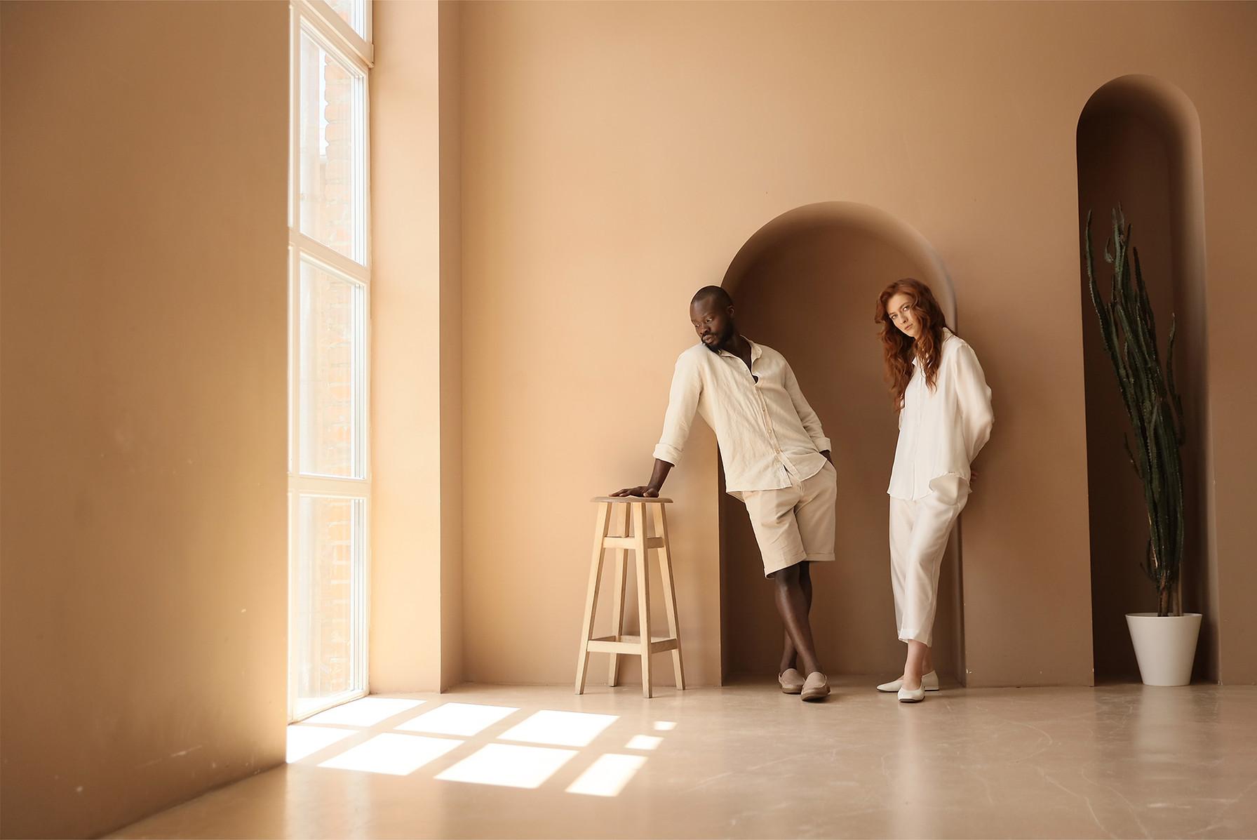 Achtergrondafbeelding van een redactioneel shot van twee mensen in een minimalistisch ontworpen kamer, gekleed in lichtgekleurde linnen kleding.