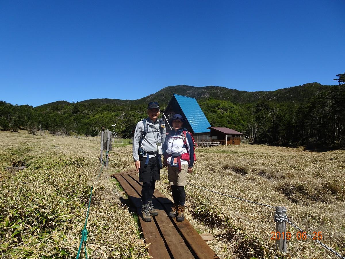 青い空と草原の山小屋