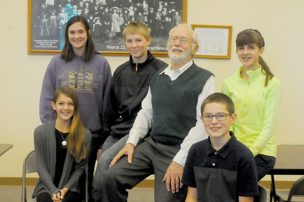 Father Tony Kroll, a long-time investor in microloans, visited with youth at Holy Cross Parish in Butler Nov. 20. Pictured with him are: front from left, Kami Steinbach and Jack Peeters, from left back, Molly Swanz, Abe Carlson and Kalli Steinbach. Not pictured are Ben Minton, Jimmy Minton and Grace Minton Photo: Diane Towalski.