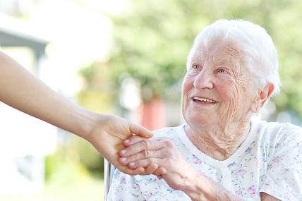 smiling elderly lady shaking hands with her carer