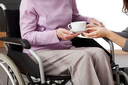 elderly lady in wheelchair being given a cup of tea by her carer