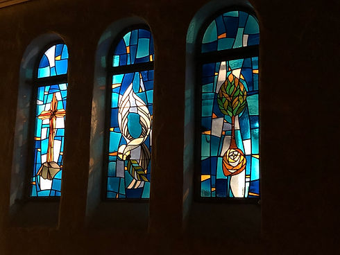 Three stained glass arched windows showing the cross, a dove, and a tree.