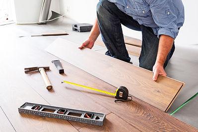 Man installing new laminated wooden floo