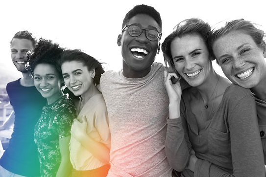 A diverse polycule of six people stand outdoors, each smiling and laughing together, facing the viewer. A rainbow of light shines up at them.