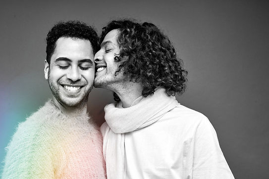 Two people with facial hair smile with their eyes closed, while a rainbow of light shines up at them. One faces the viewer, and the other presses their smile into their partner's face.