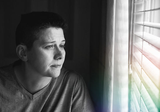 A person with short hair, wearing a t-shirt and a solemn expression, looks out a window into the distance. A rainbow of light shines through the window.