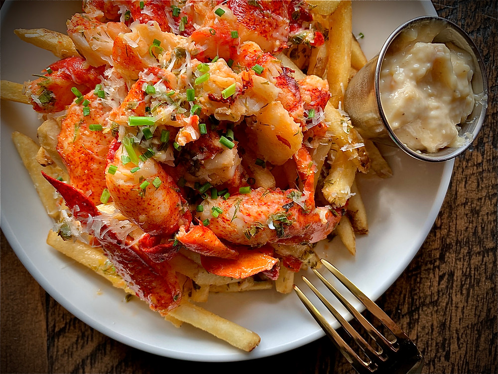 a plate of fries smothered in lobster