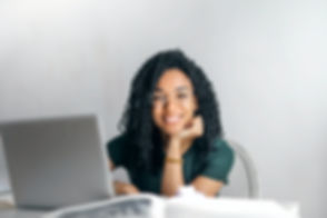 happy-ethnic-woman-sitting-at-table-with