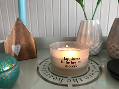 Candle with text: Happinsess is the key to success