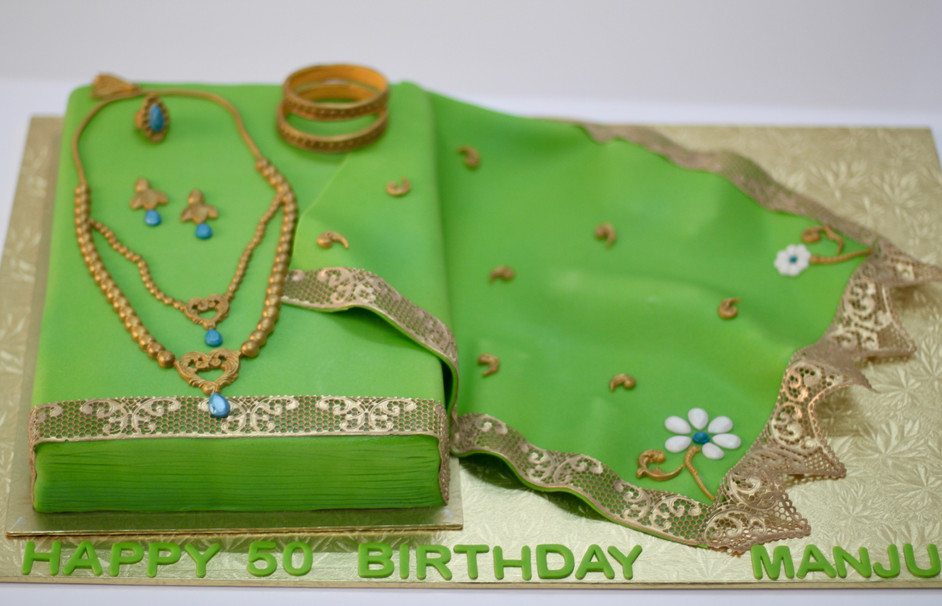 A saree cake with all edible gold lace and fondant jewelery