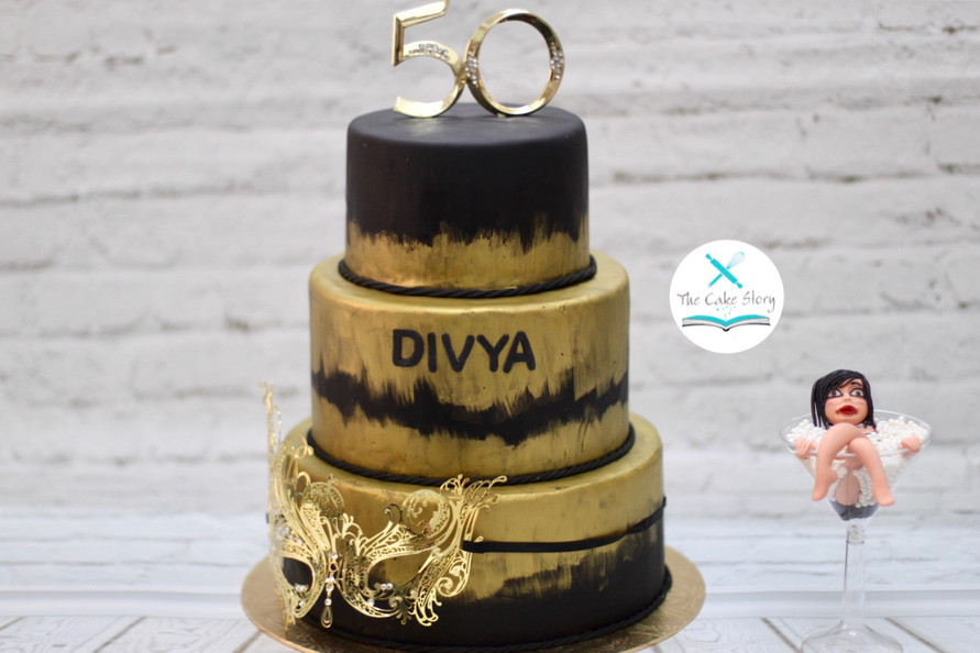 A black and gold themed cake for a 50th birthday celebration of the same theme.