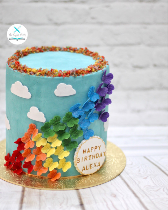A Rainbow cake inside continuing the rainbow theme on the outside with the butterflies