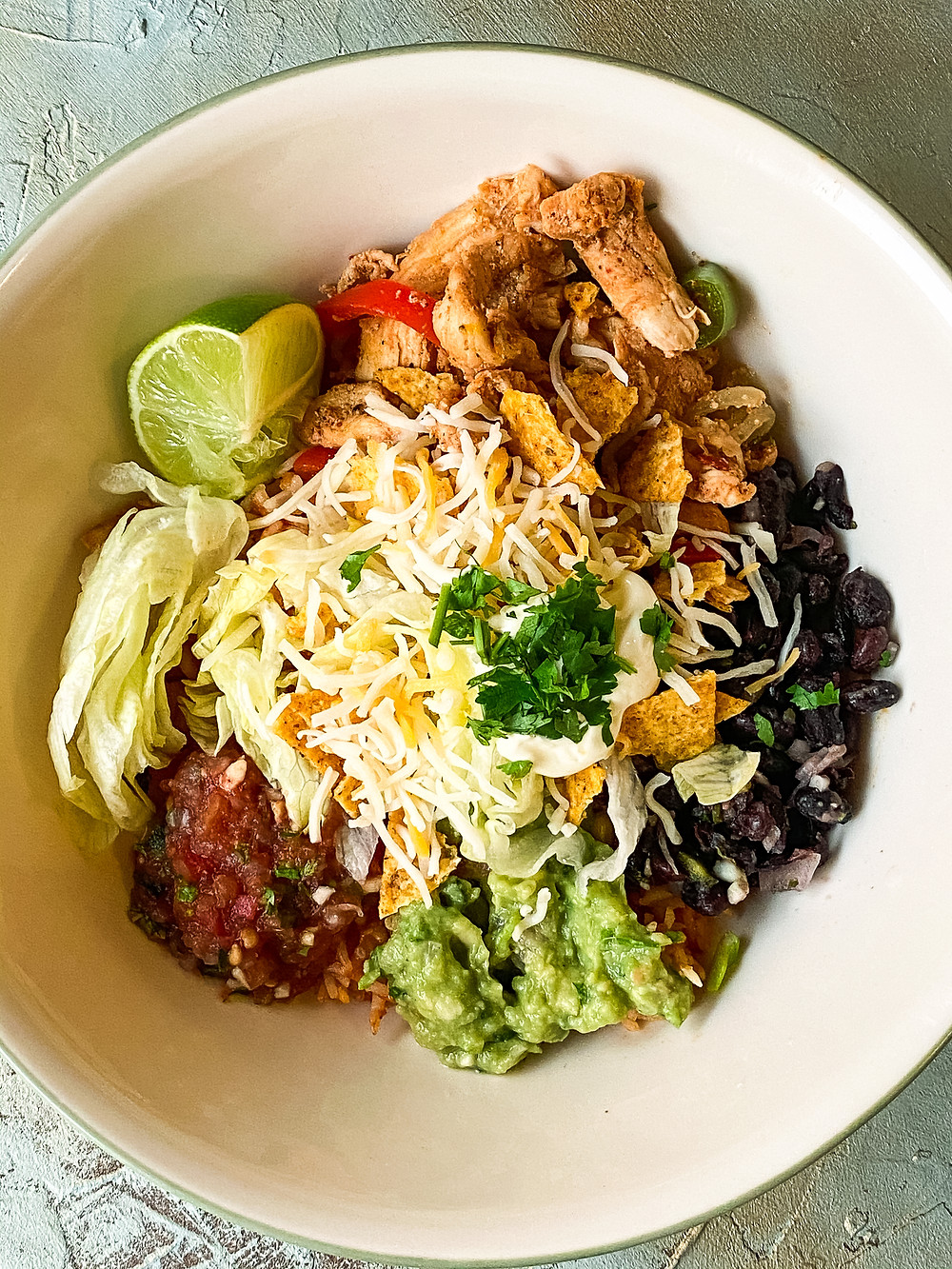 chicken burrito bowl consisting of Mexican rice, Chicken Fajita, Guacamole, Salsa, Black Bean salsa