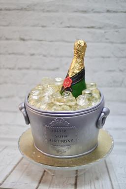 A champange bottle in an ice bucket cake.