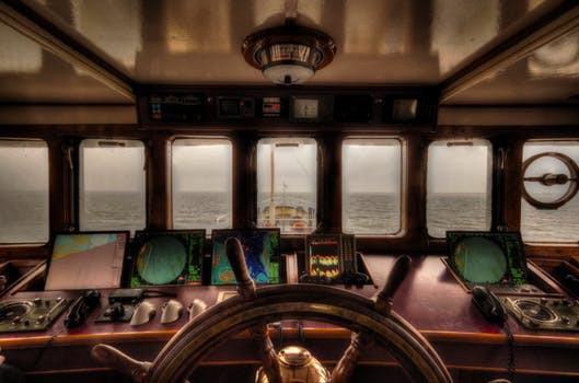 Ship's wheel looking out bridge window of a ship