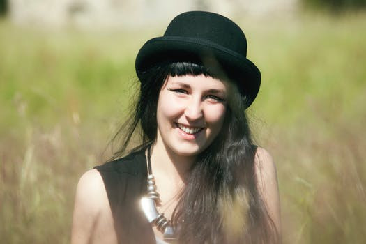 smiling woman wearing a hat sitting in a field