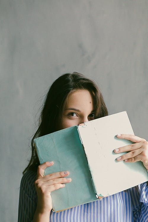 woman hiding part of face behind book
