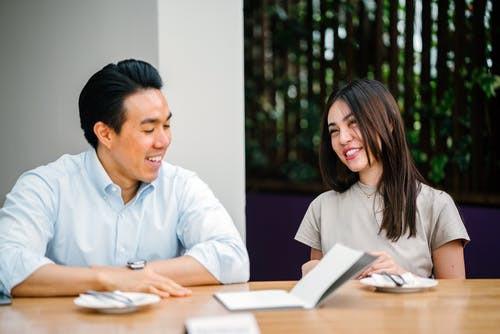 man and woman talking at a table