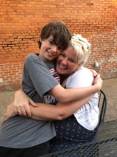 Smiling teenage boy sitting on smiling woman's lap in an embrace