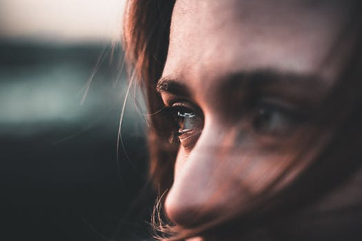 Woman's partially shielded face with eyes showing signs of emotion