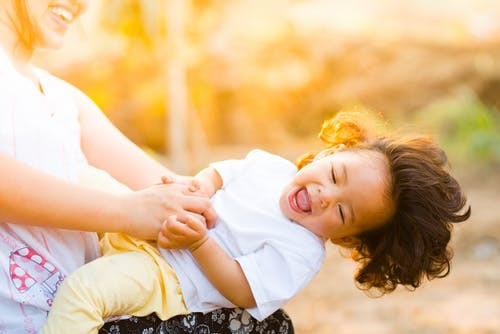 Smiling child being played with by a woman