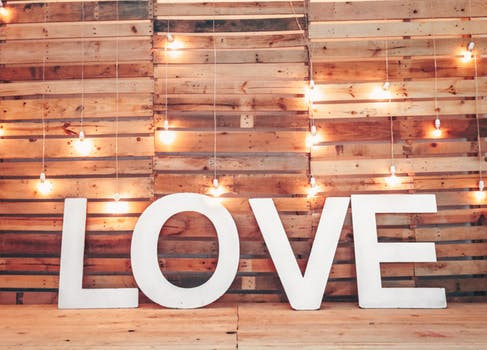 Sign of LOVE in front of a wood picket wall