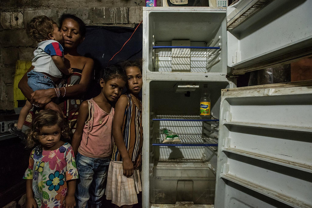 Leidy Cordova, 37, with four of her five children at their home in Cumaná, Venezuela, last week. Their broken refrigerator held the only food in the house: a bag of corn flour and a bottle of vinegar.