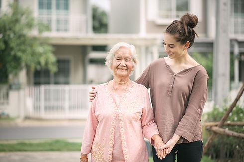 woman-walking-embracing-asian-elderly-wo