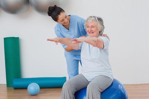 instructor-assisting-senior-woman-exerci