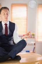 calm-businessman-meditating-in-lotus-pos