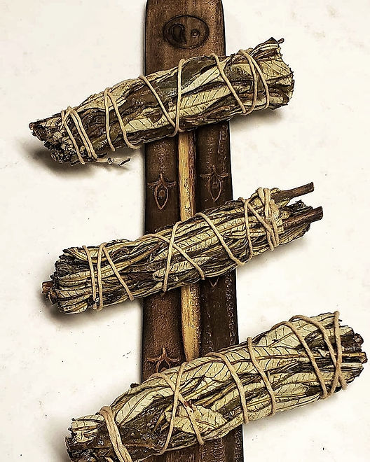 A trio of yerba santo bundles on a beautifully carved incense tray.
