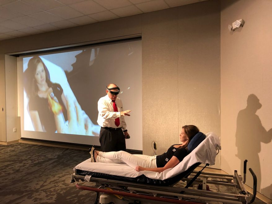 Dr. Wendell Gibby (left), CEO of health care technology firm Novarad, demonstrates how an augmented reality device can depict a CT scan as a hologram onto a patient at George Washington University Hospital in Washington on Monday. (Shen Wu Tan/ The Washington Times)