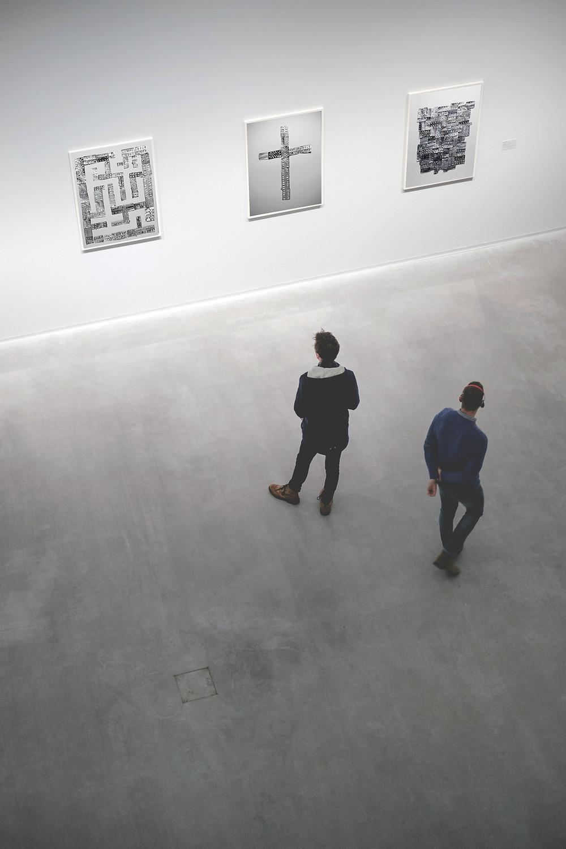 Two men look at art in an art exhibit.