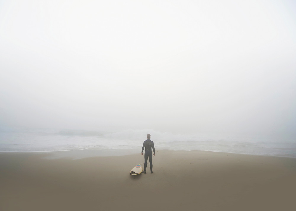 man standing alone, looking out on an expansive ocean, perhaps feeling isolated.