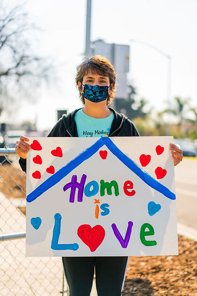 """Volunteer holding """"home is love"""" sign"""