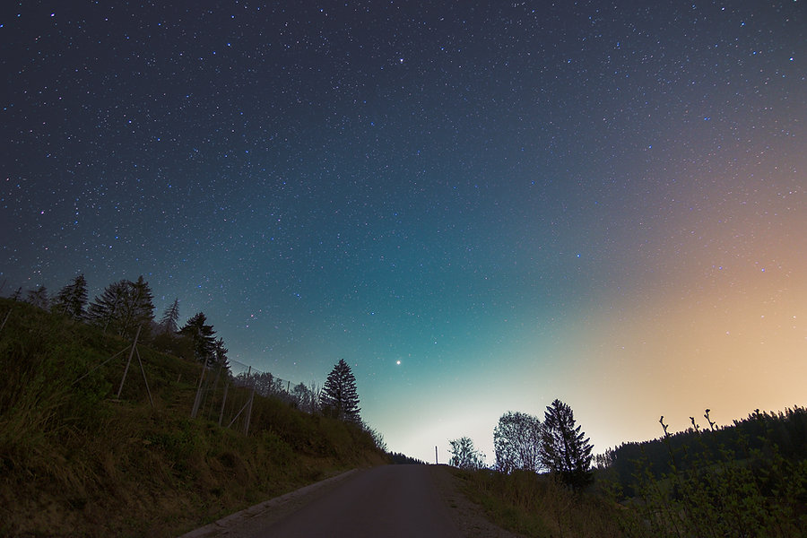Starry night sky above the road in small
