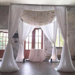 Gorgeous ceremony chuppah adorned with a handmade Jewish tapestry! #pensacolaweddings #weddingwalls