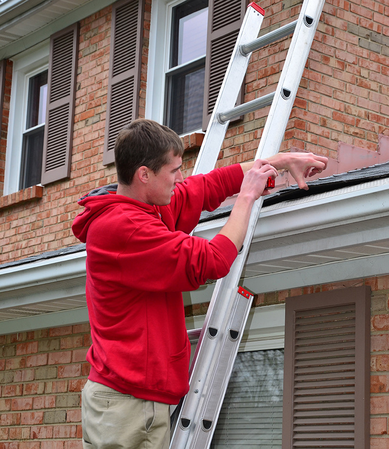 Roofing salesman inspecting shingles and gutters for hail damage