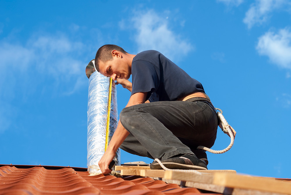 Roofing contractor measuring roof ventilation during an install