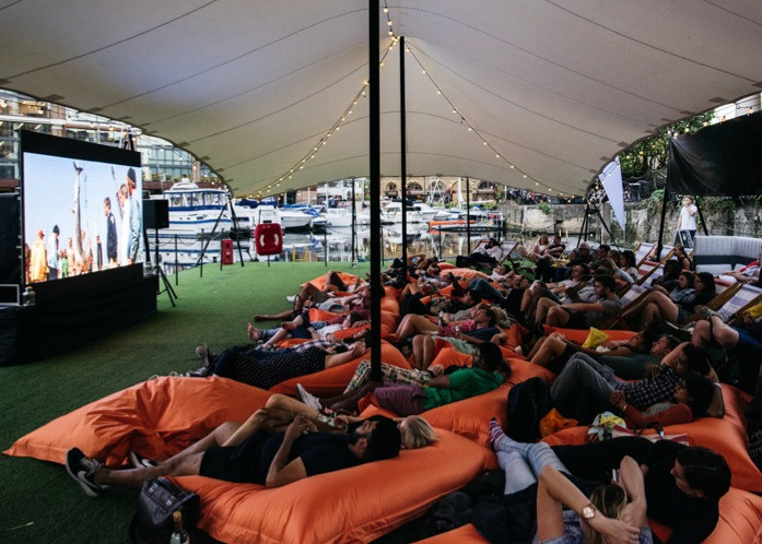 Crowds sit back and relax on bean bags watching a film at the Floating Film Festival at St Katherine's docks