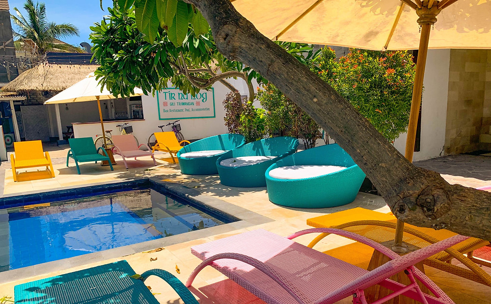 Colourful lounge chairs beside a hotel pool waiting for you to nap on them