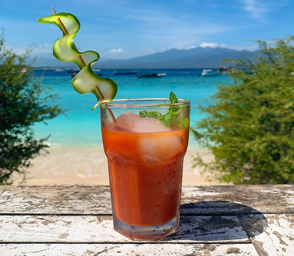 A fancy looking bloody mary with turquoise blue waters behind it