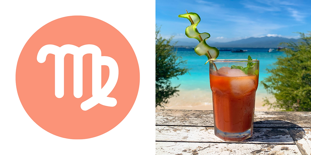 A red Bloody Mary with a beautifully curled slice of cucumber on a stick hanging out on the beach